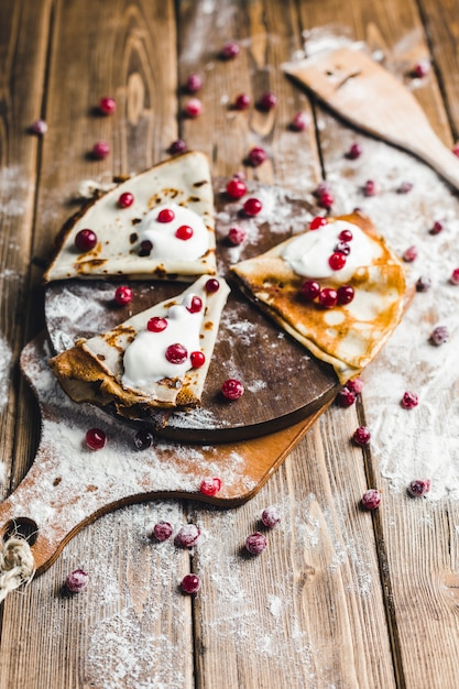 Crêpes aux canneberges et crème sure sur une planche de bois en farine Photo Premium