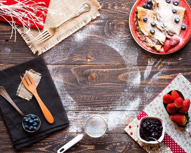 Crêpes aux fraises fraîches ou crêpes aux fruits et au chocolat sur fond en bois Photo Premium