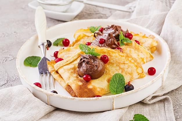Crêpes Aux Fruits Rouges Et Au Chocolat, Décorées De Feuilles De Menthe Photo Premium