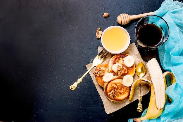 Crêpes à la banane, noix, miel et tasse de café sur fond sombre Photo Premium