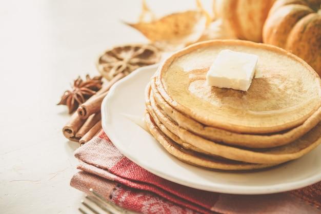 Crêpes à la citrouille sur une assiette blanche avec du beurre et du miel Photo Premium