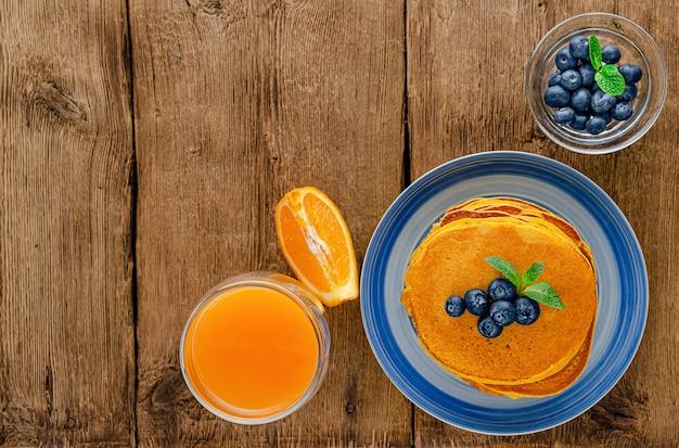Crêpes à La Citrouille Aux Bleuets Et Jus D'orange Sur Une Table En Bois Rustique. Copiez L'espace. Aérien Photo Premium
