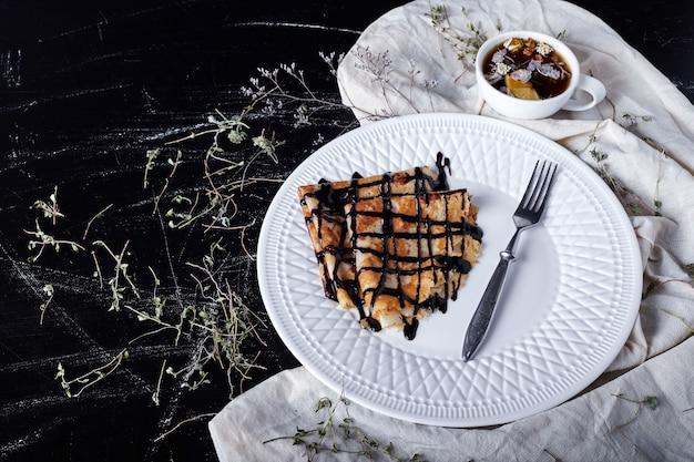 Crêpes Dans Une Assiette Blanche Avec Du Sirop De Chocolat Et Du Thé. Photo gratuit