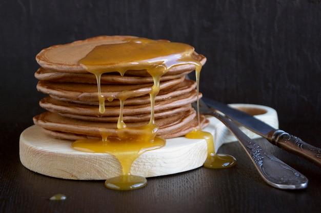 Crêpes faites maison au miel sur fond noir. Photo Premium