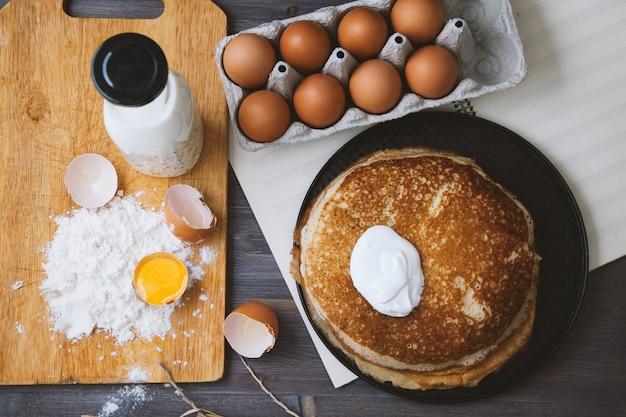 Crêpes fraîches et chaudes dans une poêle à frire, œufs, lait, farine sur une table en bois. vue de dessus Photo Premium