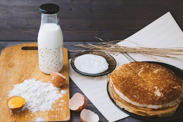 Crêpes Fraîches Et Chaudes Dans Une Poêle à Frire, œufs, Lait, Farine Sur Une Table En Bois. Photo Premium