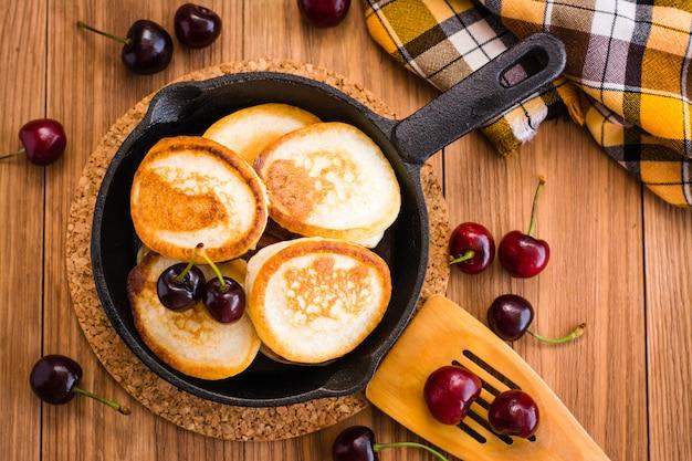 Crêpes Frites Dans Une Poêle En Fer Et Des Cerises Mûres Sur Une Table En Bois. Vue De Dessus Photo Premium