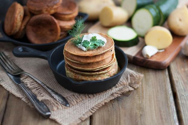 Crêpes De Légumes Dans Une Poêle En Fonte Sur Un Fond En Bois Photo Premium