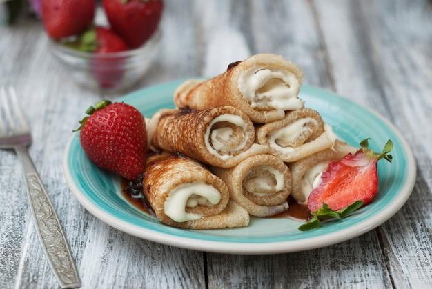 Crêpes roulées à la fraise. petit déjeuner. Photo Premium
