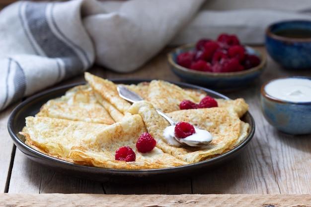 Crêpes Servies Avec Crème Sure, Framboises Et Miel. Le Plat Traditionnel Du Carnaval Et Du Maslenitsa. Photo Premium