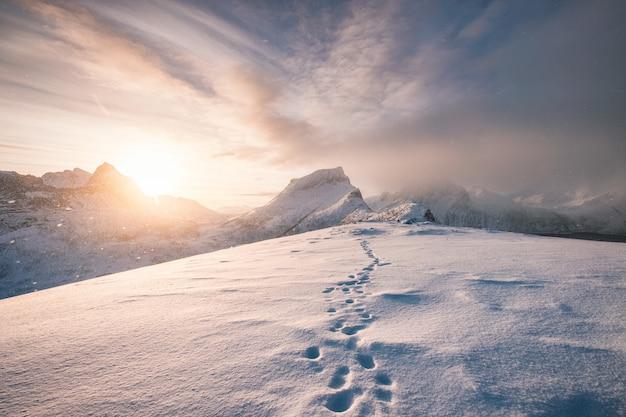 Crête de montagne enneigée avec empreinte dans le blizzard Photo Premium