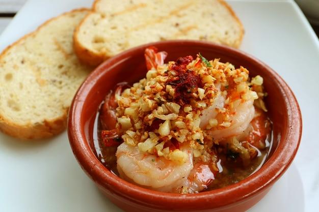 Crevettes à l'ail ou gambas al ajillo, style espagnol, avec tranches de pain tranchées floues en arrière-plan Photo Premium