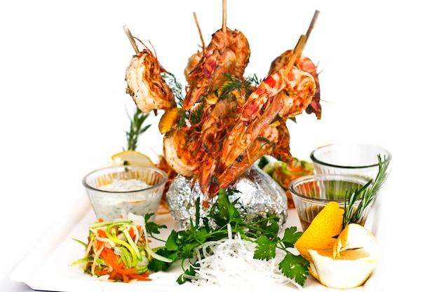Crevettes géantes cuites sur des brochettes en bois. servir avec des sauces et des herbes sur une assiette blanche. Photo Premium