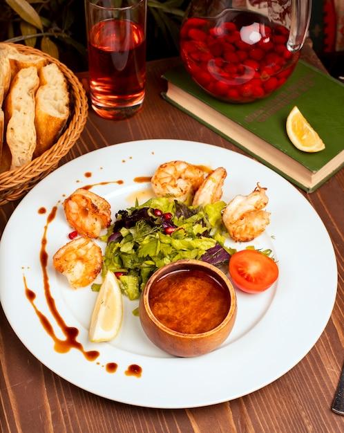 Crevettes grillées avec salade verte, tomates, citron et sauce dans une assiette blanche. Photo gratuit