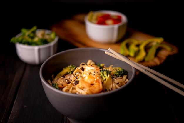 Crevettes sur nouilles dans un bol avec avocat et baguettes Photo gratuit