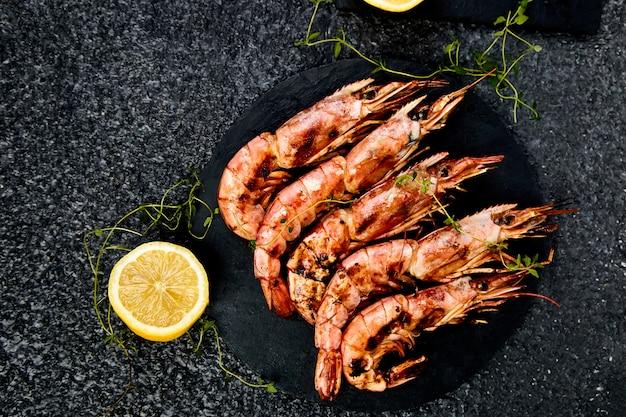 Crevettes tigrées grillées sur une plaque d'ardoise noire Photo Premium