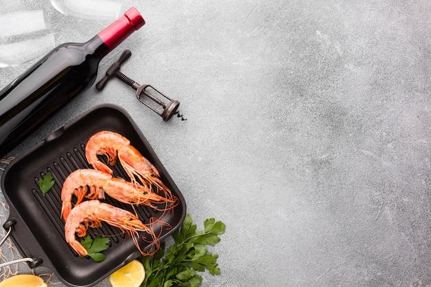 Crevettes vue de dessus sur le pan avec une bouteille de vin Photo gratuit
