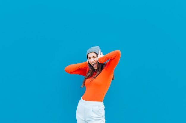 Criant femme avec ses mains sur l'oreille portant chapeau tricoté sur fond bleu Photo gratuit