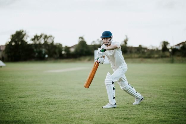 Cricketer sur le terrain en action Photo Premium