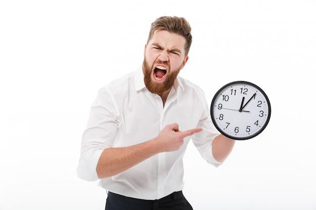 Crier L'homme En Tenue D'affaires Tenant Et Pointant Sur Horloge Photo gratuit