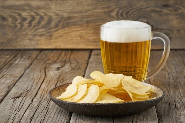 Crisp dans un bol avec de la bière dans un verre, vue de dessus, en bois, espace de copie Photo Premium