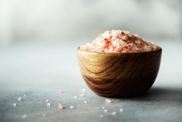 Cristaux de sel rose de l'himalaya et poudre dans des bols en bois sur béton gris. alimentation saine sans sel. Photo Premium