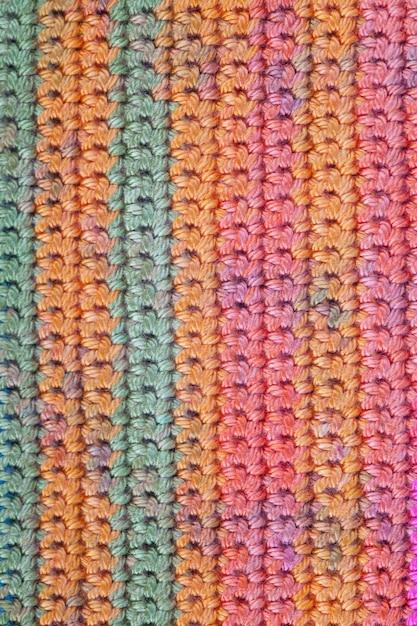 Crochet, fait à la main, travaux d'aiguille. bouchent la texture de fond macro de texture tricotée rayée. Photo Premium