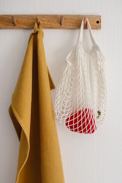 Crochet De Suspension Avec Sac écologique Blanc Avec Un Poivron Et Une Serviette En Coton Jaune, Accroché Sur Un Mur Blanc Dans La Cuisine Moderne Photo Premium