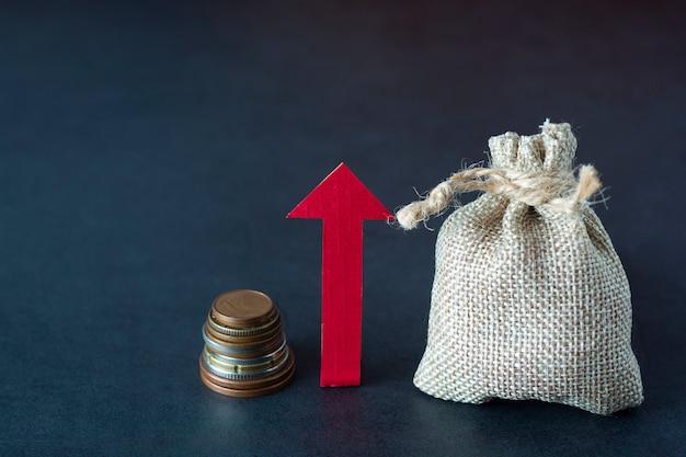 Croissance, augmenter ou augmenter vos revenus avec flèche directionnelle, argent et un sac sur dark. financière. fond Photo Premium
