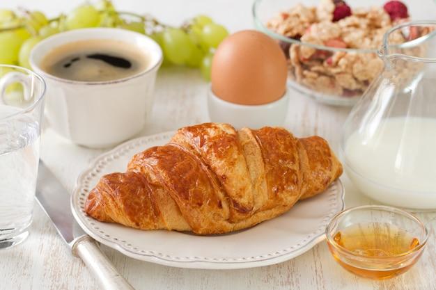Croissant au lait, oeuf, café sur une surface en bois blanche Photo Premium
