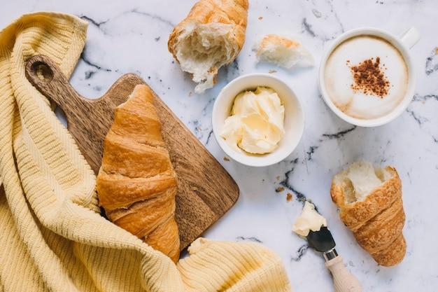 Croissant; beurre et tasse à café sur le dessus en marbre avec serviette jaune Photo gratuit
