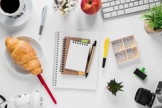 Croissant cuit au four; tasse de pomme et thé avec papeterie sur bureau blanc Photo gratuit