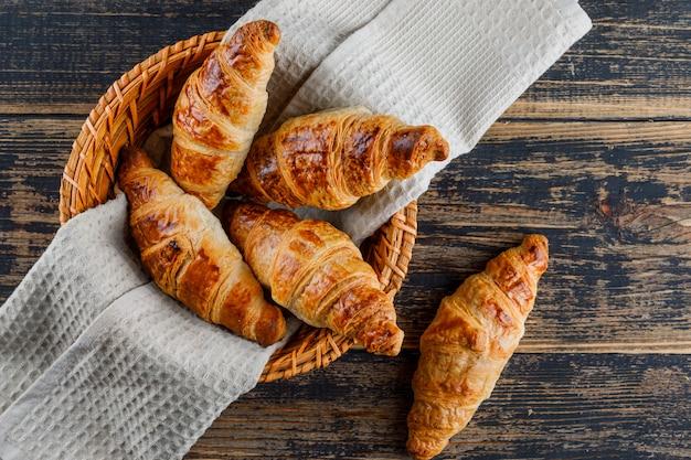 Croissant Dans Un Panier Avec Un Chiffon Sur Une Table En Bois. Pose à Plat. Photo gratuit