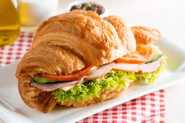Croissant frais ou sandwich à la salade, jambon sur fond en bois. Photo Premium