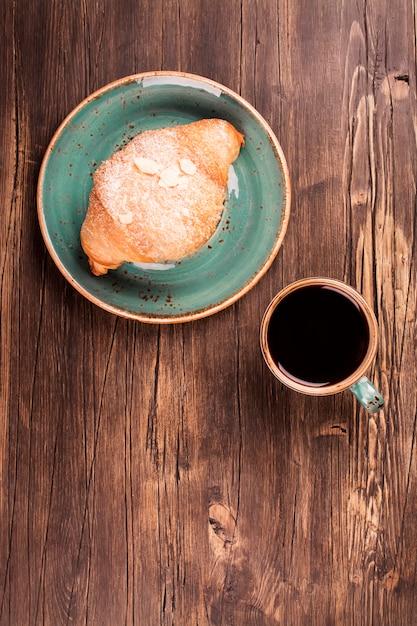 Croissant frais et tasse de café noir Photo Premium