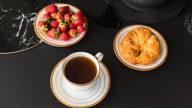 Croissant et fraises avec du thé sur la table Photo gratuit
