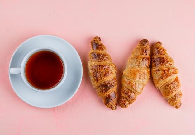 Croissant Avec Tasse De Thé Plat Posé Sur Une Table Rose Photo gratuit