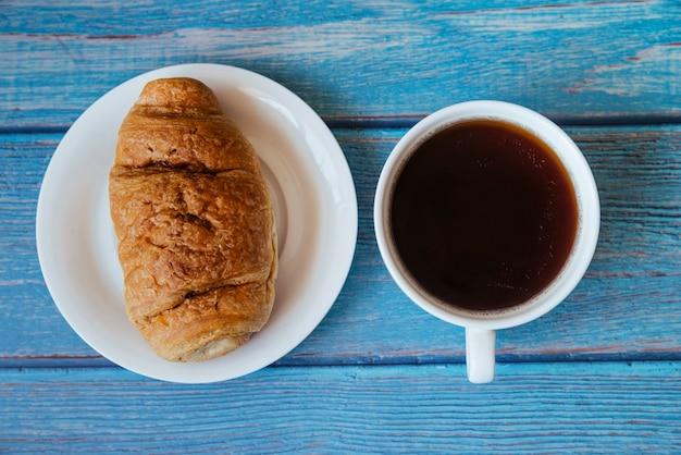 Croissant vue de dessus et café sur une table en bois Photo gratuit