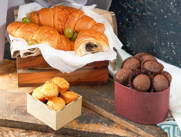 Croissants au chocolat, boîte de pralines et muffins sur un morceau de bois Photo gratuit