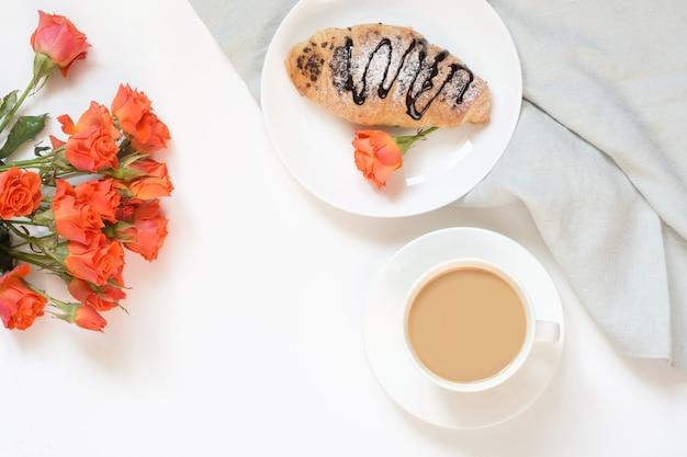 Des croissants au chocolat et une tasse de café sur une table blanche. vue de dessus. petit déjeuner féminin. espace de copie. Photo Premium