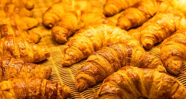 Croissants Dans Une Boulangerie. Croissants Fraîchement Cuits Au Four Sur Fond De Texture Photo Premium