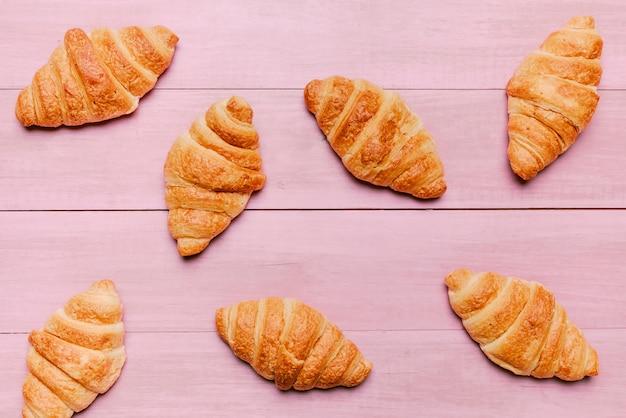Croissants dispersés sur une table rose Photo gratuit