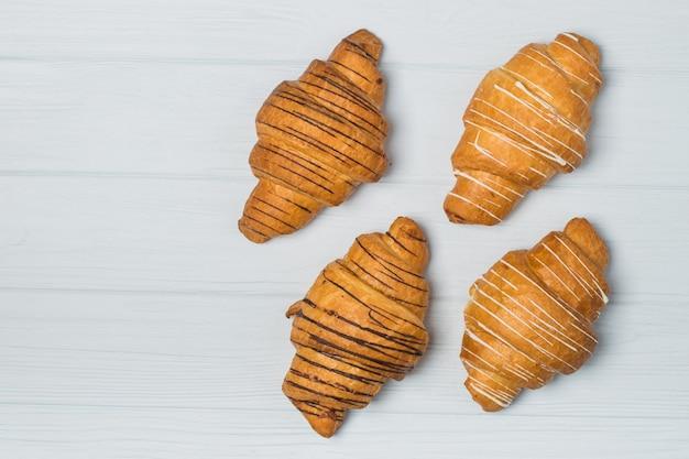 Croissants fraîchement sortis du four et tasse à café sur la table grise, vue de dessus Photo Premium
