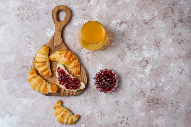 Des croissants frais et savoureux faits maison avec de la confiture de framboises sur du gris-blanc. patisserie française Photo gratuit