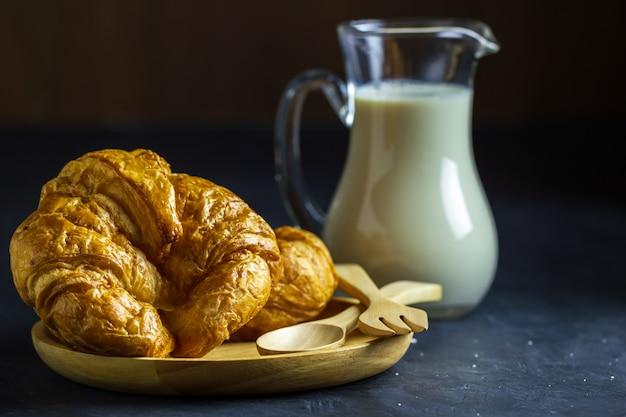 Croissants Sur Un Plat En Bois Et Pot à Lait Sur Une Table Sur Fond Sombre. Photo Premium