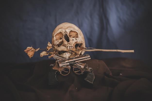 Croix pistolet et un crâne dans la bouche avec des fleurs sèches Photo gratuit