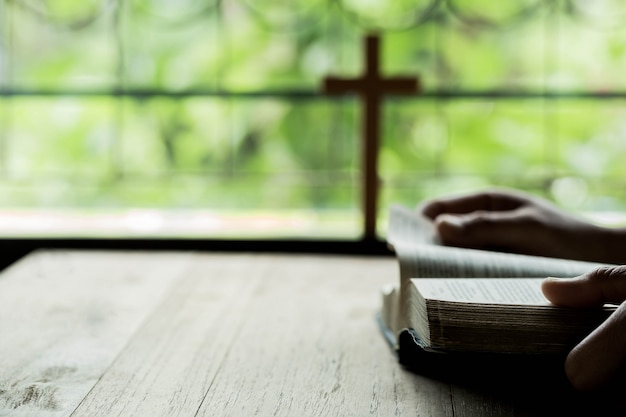 Croix qui s'ouvrent au dessus de la bible sur une table en bois Photo gratuit