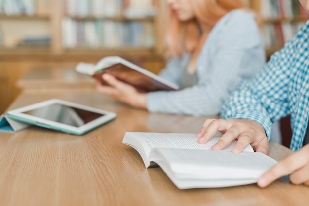 Crop Adolescents Lisant Dans La Bibliothèque Photo gratuit