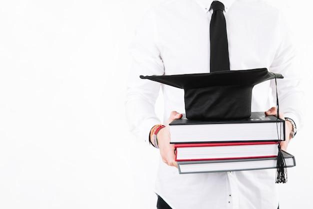 Crop alumnus avec des livres et une casquette Photo gratuit