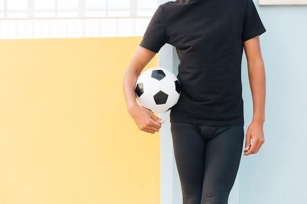 Crop black homme debout et tenant le football Photo gratuit